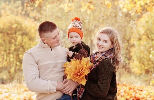 Família feliz com bebezinho no parque outono