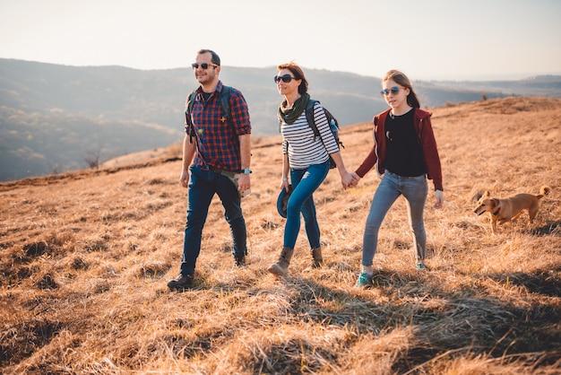 Família feliz com cachorro caminhadas na montanha