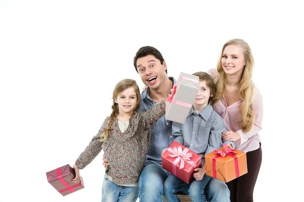 Família feliz com caixa de presente isolada no fundo branco.