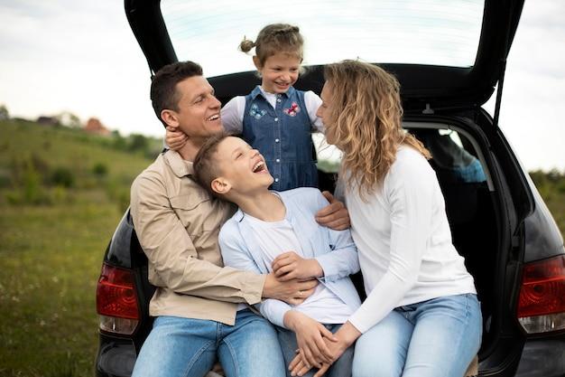 Família feliz com carro em plano médio