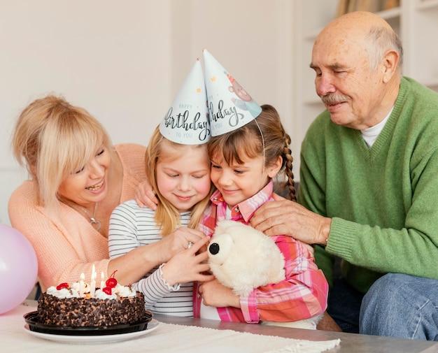 Família feliz com chapéu de festa em foto média