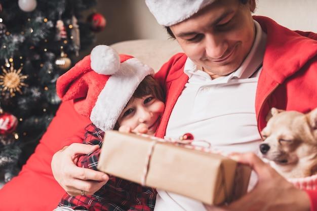 Família feliz com chapéu de papai noel, pai e filho dando um presente de natal em casa