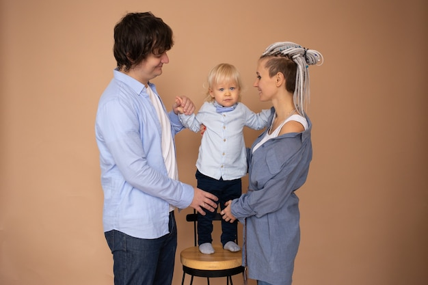 Família feliz com criança brincando isolada em bege