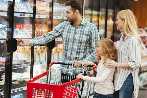 Família feliz com criança e carrinho de compras, comprando comida