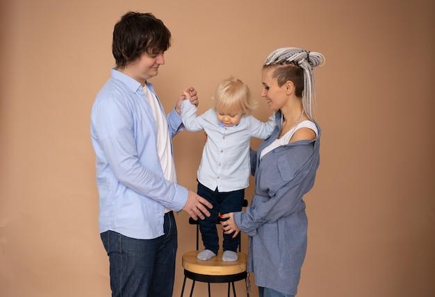 Família feliz com criança isolada em parede bege