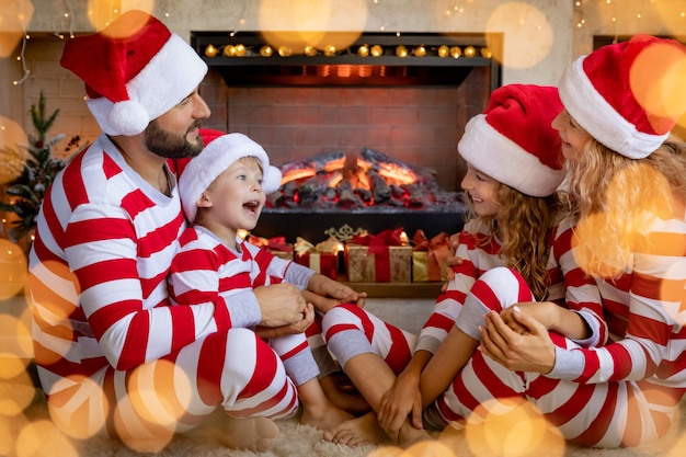 Família feliz com crianças de pijama listrado perto da lareira no natal. mãe, pai e filhos se divertindo em casa.