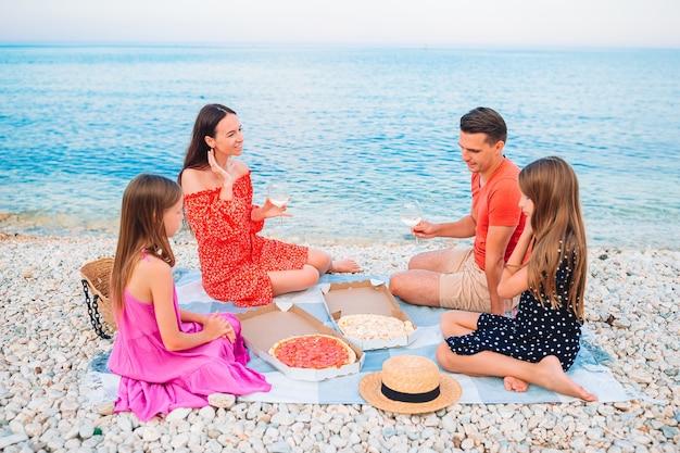 Família feliz com crianças na praia fazendo piquenique