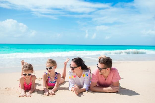 Família feliz com crianças na praia junto