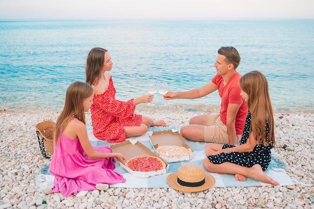 Família feliz com crianças na praia no piquenique