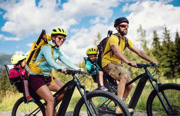Família feliz com crianças pequenas, andar de bicicleta ao ar livre na natureza de verão, altos tatras, na eslováquia.