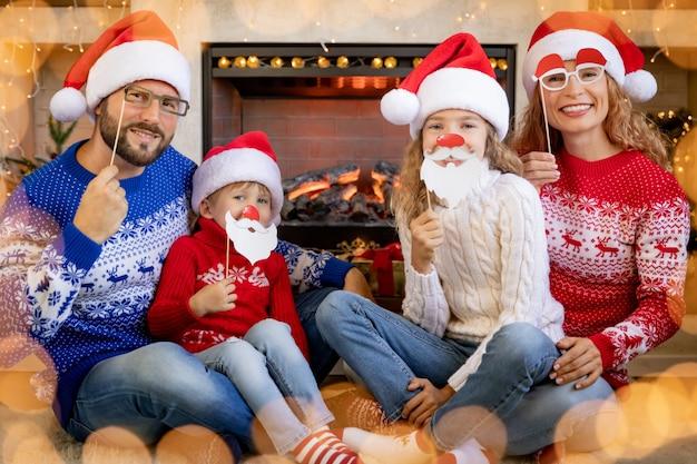 Família feliz com crianças perto da lareira no natal. mãe, pai e filhos se divertindo em casa.