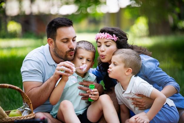 Família feliz com crianças soprando bolhas de sabão ao ar livre
