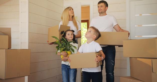 Família feliz, com dois filhos em nova casa. mãe pai e filho em casa nova