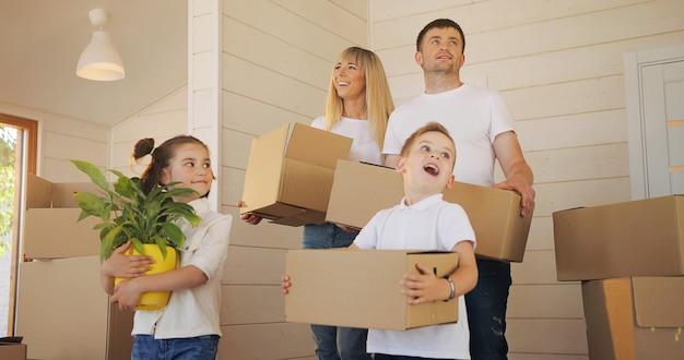Família feliz, com dois filhos em nova casa segurando caixas