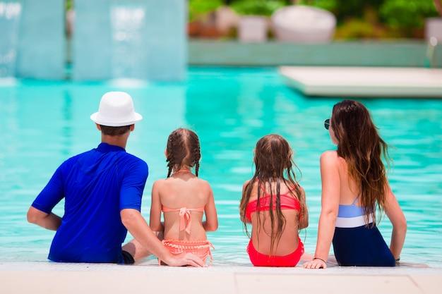 Família feliz, com dois filhos na piscina.