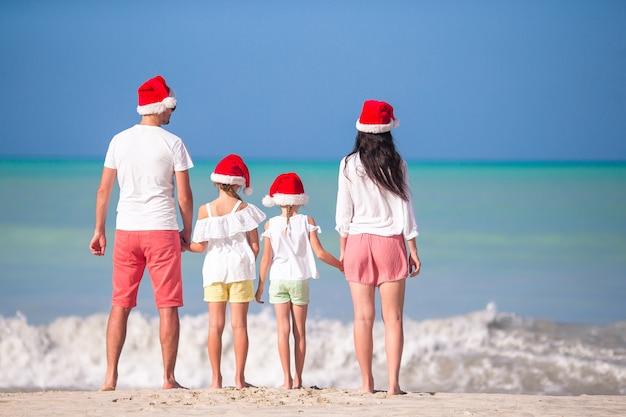 Família feliz, com dois filhos no chapéu de papai noel nas férias de verão
