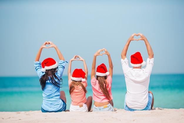 Família feliz com dois filhos no chapéu do papai noel nas férias de verão