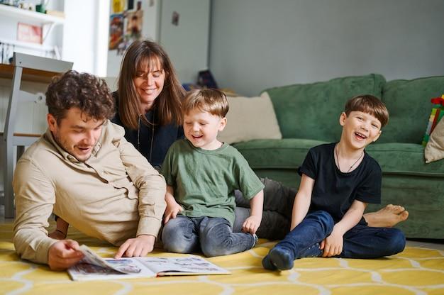 Família feliz com dois filhos pequenos lendo histórias dentro de casa, pais com filhos passando um tempo juntos e deitados no chão em casa