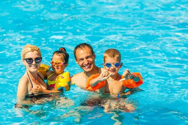Família feliz, com dois filhos se divertindo na piscina.