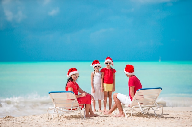 Família feliz com duas crianças no chapéu de papai noel em férias de verão