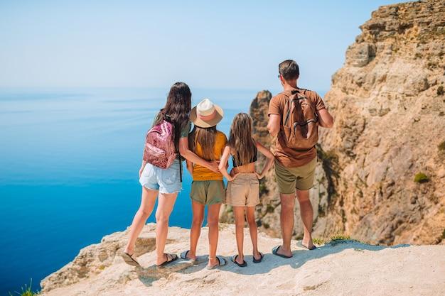 Família feliz com duas garotas caminhando nas montanhas