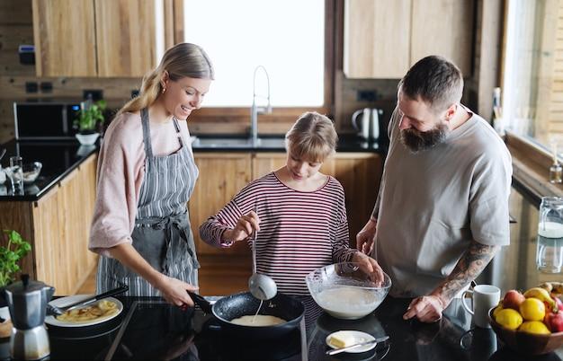 Família feliz com filha pequena cozinhando dentro de casa, férias de inverno em apartamento privado.