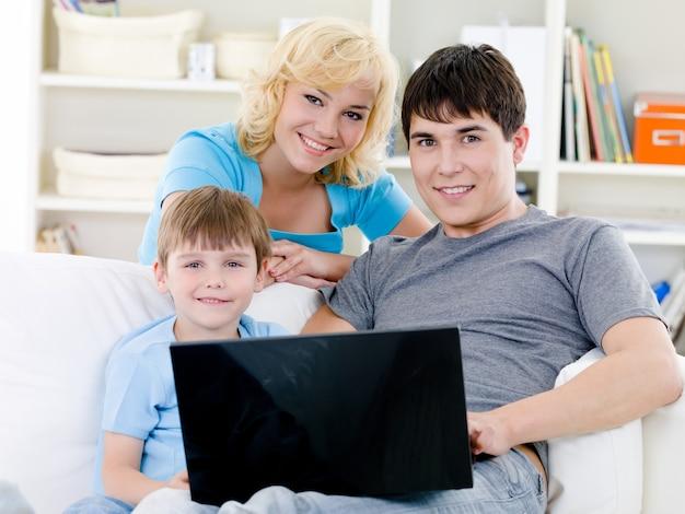 Família feliz com filho e laptop em casa