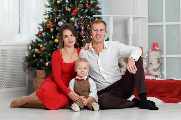 Família feliz com filho pequeno sentado perto da árvore de natal ano novo