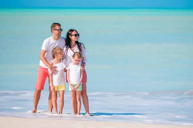 Família feliz com filhos a pé na praia