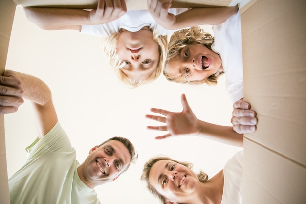 Família feliz com filhos fofos abrindo uma caixa de papelão em movimento e olhando para dentro