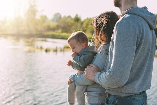 Família feliz com menino bonito no lago