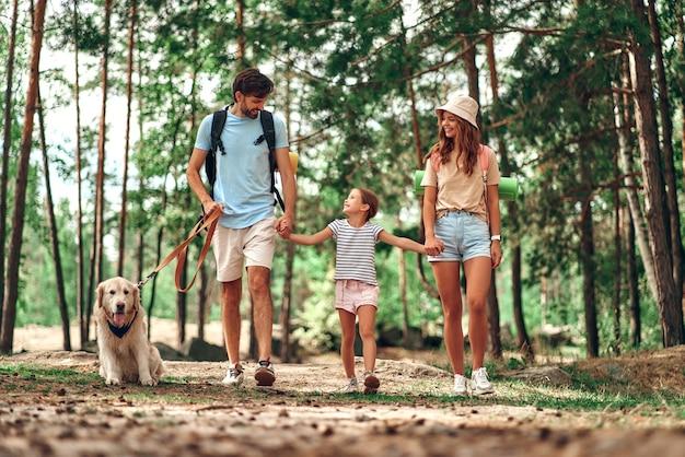 Família feliz com mochilas e cachorro labrador está andando na floresta. mãe, pai e filha no fim de semana. acampar, viajar, fazer caminhadas.