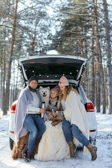 Família feliz com o cachorro de férias durante as férias de inverno, perto da estrada. vestida com roupas quentes, sentada no porta-malas de um carro e tomando chá em uma garrafa térmica. espaço para texto. férias de inverno