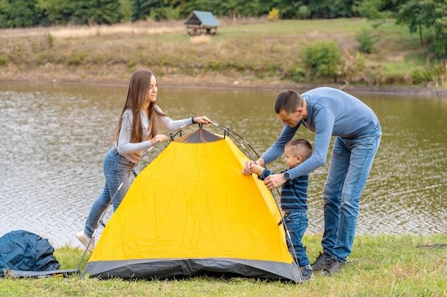 Família feliz com o filho pequeno configurar barraca de acampamento. infância feliz, viagem de acampamento com os pais. uma criança ajuda a montar uma barraca