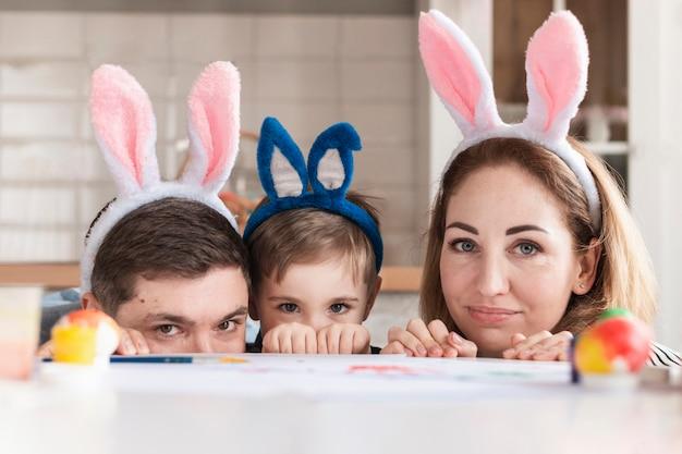 Família feliz com orelhas de coelho posando
