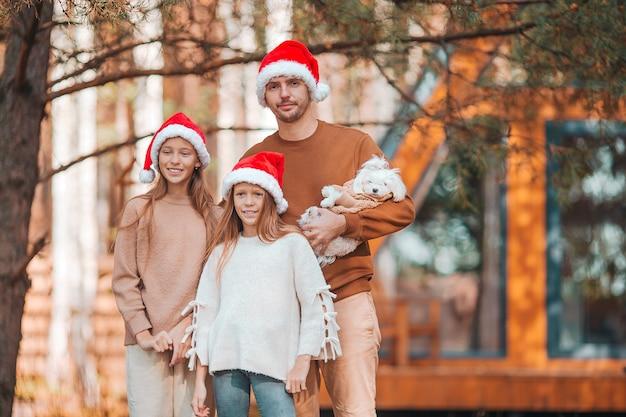 Família feliz com pai e filhos com chapéu de papai noel aproveitando as férias de natal