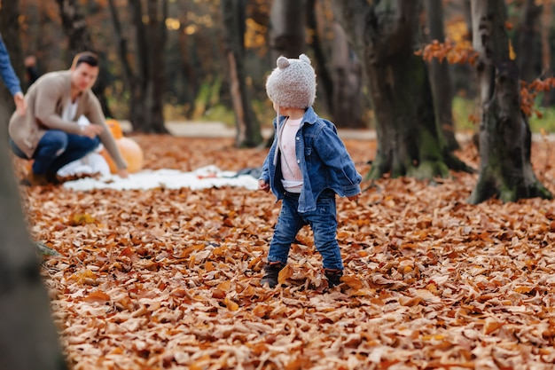 Família feliz, com, pequeno, cute, criança, parque, ligado, folha amarela, com, grande, abóbora, em, outono