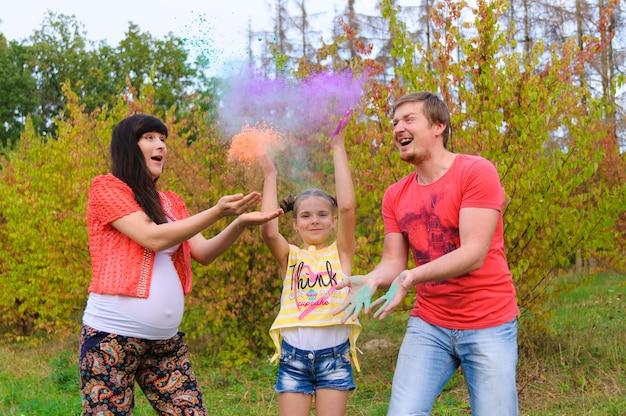 Família feliz com rostos pintados de holi