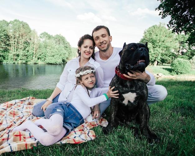 Família feliz com seu cachorro sentado na grama perto do rio. o conceito de felicidade familiar