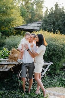 Família feliz com seu filho caminhando no parque ao pôr do sol. felicidade. ame