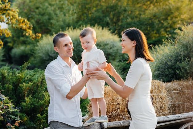 Família feliz com seu filho caminhando no parque ao pôr do sol. felicidade. ame.