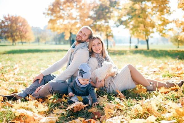 Família feliz com seu retrato ao ar livre do bebê no parque outono