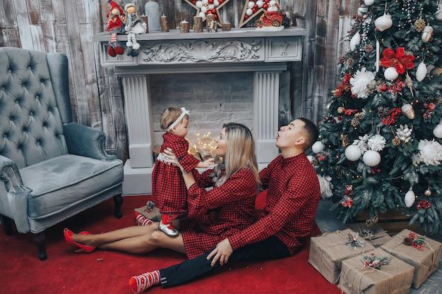 Família feliz com sua filha junto no quarto decorado com uma árvore de natal