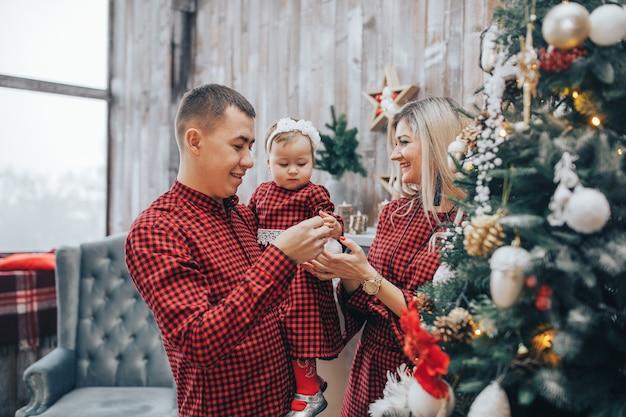 Família feliz com sua filha junto no quarto decorado