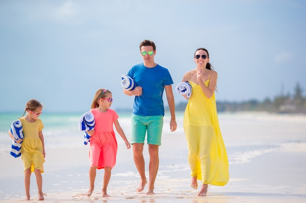 Família feliz com toalha e curtindo férias na praia tropical com areia branca e água azul-turquesa do oceano
