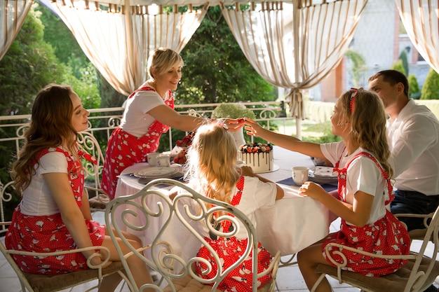 Família feliz, com três filhas, bebendo chá em casa