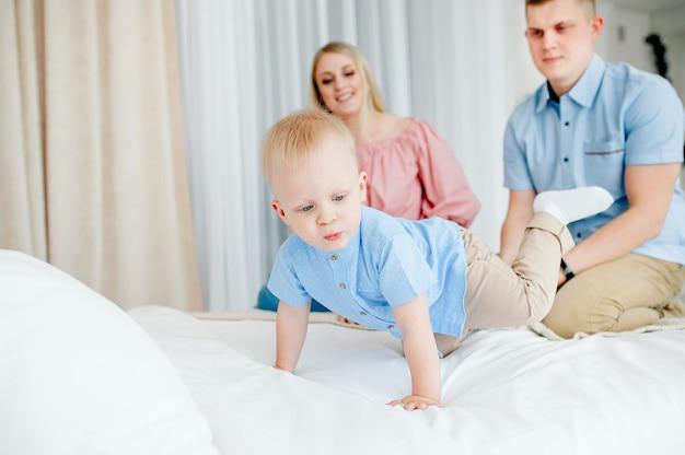 Família feliz com um bebê fofo. mãe, pai e filho estão brincando na cama em um quarto bem iluminado e aconchegante em casa.