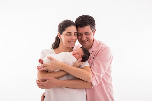 Família feliz com um bebê recém-nascido em um fundo branco.