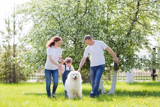 Família feliz com um cachorro branco em um parque de verão.