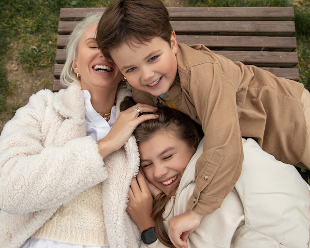 Família feliz com um dos pais ao ar livre na grama no outono, rostos sorridentes, todos deitados se divertindo